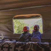 Two boys look out of the window from inside a Camp365
